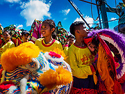 """02 JUNE 2017 - SAMUT SAKHON, THAILAND:  Children in a Lion dance troupe prepare to get off a boat after the procession on the Tha Chin River in Samut Sakhon. The Chaopho Lak Mueang Procession (City Pillar Shrine Procession) is a religious festival that takes place in June in front of city hall in Samut Sakhon. The """"Chaopho Lak Mueang"""" is  placed on a fishing boat and taken across the Tha Chin River from Talat Maha Chai to Tha Chalom in the area of Wat Suwannaram and then paraded through the community before returning to the temple in Samut Sakhon. Samut Sakhon is always known by its historic name of Mahachai.     PHOTO BY JACK KURTZ"""