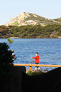 View from Sanary over the sea to the St Pierre des Embiez island a person in red walking with poles Le Brusc Six Fours Var Cote d'Azur France