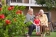 Senior Woman Sitting on a Bench Enjoying the Outdoors with her Daughter and Granddaughter