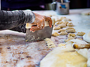 07 NOVEMBER 2017 - BANGKOK, THAILAND: Cutting pa tong go dough before putting it in a wok to fry (Chinese friend dough, like a Chinese churro or donut) at a local market on Ekkamai Soi 30 in Bangkok.      PHOTO BY JACK KURTZ