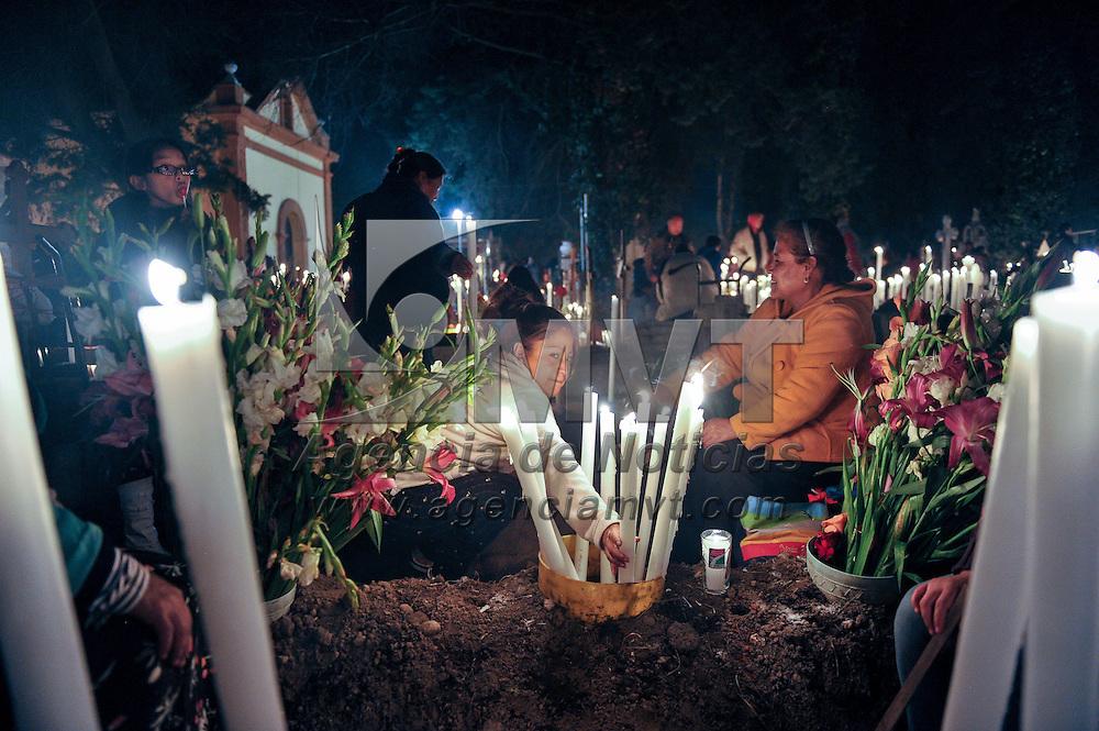 Toluca, Méx.- Miles de personas velan al pie de la tumba de sus familiares durante la tradicional noche de muertos en el panteón de Santa Ana Tlapaltitlán. Agencia MVT / Mario Vazquez de la Torre.