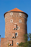 a vertical shot of the sandomierz tower at the wawel castle in bright sunshine and blue sky behind