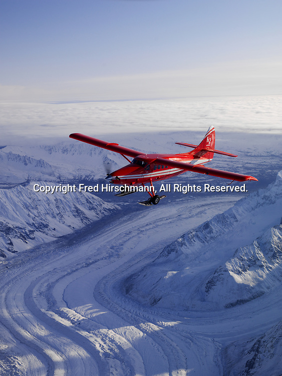 K2 Aviation's Turbo Otter on wheel skis flying above the Yentna Glacier in Denali National Park and Preserve, Alaska.