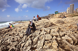 """Lebanese Kurds and a Syrian girl relax on the rocks off the Mediterranean Sea, Beirut, Lebanon, March 26, 2006. The Kurds were out for Nayrouz, """"New Day,"""" the traditional Kurdish celebration of spring."""
