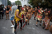 Dancing behind one of the parade sound systems. Notting Hill Carnival in West London. A celebration of West Indian / Caribbean culture and Europe's largest street party, festival and parade. Revellers come in their hundreds of thousands to have fun, dance, drink and let go in the brilliant atmosphere. It is led by members of the West Indian / Caribbrean community, particularly the Trinidadian and Tobagonian British population, many of whom have lived in the area since the 1950s. The carnival has attracted up to 2 million people in the past and centres around a parade of floats, dancers and sound systems.