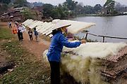 A village woman arranges rice noodles on racks to dry in So village, southwest of Hanoi, Vietnam.