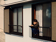 a little boy watching people from the balcony of there house