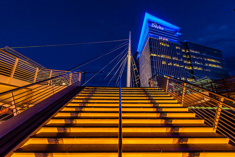 The Denver Millennium Bridge (the world's first cable-stayed bridge using post-tensioned structural construction) and the DaVita Building. The footbridge connects the 16th Street Mall with Commons Park, LoDo, Downtown Denver, Colorado USA.