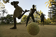 Youngsters pass the day away playing soccer on a clay yard in the mountainside above Carrefour, Haiti.