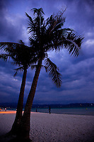 Palm trees silhouetted against stormy early evening skies on White Sand Beach, Boracay, Philippines.