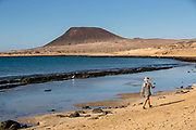 A woman walks along the sand as gentle waves break on exposed volcanic rock at low tide on 23rd November 2020, on Playa Del Salado on La Graciosa island off Lanzarote, Spain. .