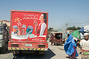 Balkh province Afghanistan. Coca cola delivery truck on the road passing woman wearing a burkha.