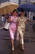 Two Chinese and European women wearing Cheongsam dresses (aka qipao) walk through Central, on their way to a handover party on the eve of the handover of sovereignty from Britain to China, on 30th June 1997, in Hong Kong, China. Midnight signified the end of British rule, and the transfer of legal and financial authority back to China. Hong Kong was once known as 'fragrant harbour' (or Heung Keung) because of the smell of transported sandal wood.