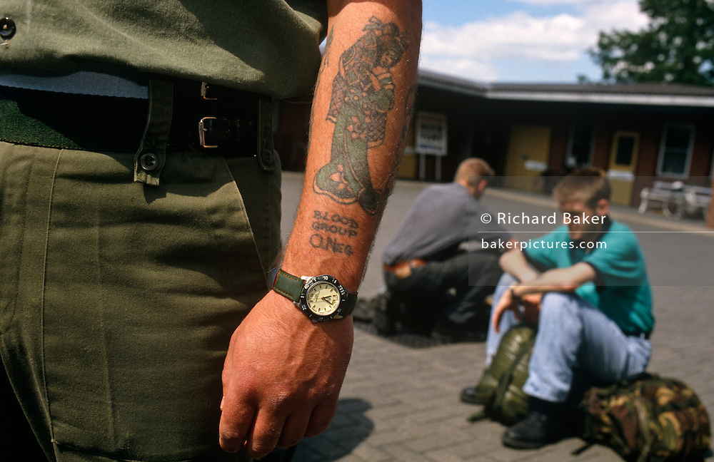 In the foreground we see the strong forearm of a British army soldier whose blood group O-Negative has been tattooed in large letters beneath an image of a Japanese Geisha girl. He also wears a watch with aq green strap matching his working army fatigues uniform. Behind him are two part-time territorial army conscripts who are sitting on their  army-issued rucksack Bergens awaiting further orders to serve on active duty from Sandhurst military academy to the Balkans during Operation Resolute, the  National Support Element to support NATO action. The dominating figure in the foreground stands upright though we don't see his face. His two conscripts sit on the ground looking dejected or perhaps worried about their forthcoming duties. They are still in civillian clothing, jeans and t-shirts but will soon change into uniform.