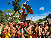 22 JULY 2016 - TENGANAN DUAH TUKAD, BALI, INDONESIA: Participants in the pandanus fights taunt their opponents in the Tenganan Duah Tukad village on Bali. The ritual Pandanus fights are dedicated to Hindu Lord Indra. Men engage in ritual combat with spiky pandanus leaves and rattan shields. They usually end up leaving bloody scratches on the combatants' backs. The young girls from the community wear their best outfits to watch the fights. The fights have been traced to traditional Balinese beliefs from the 14th century CE. The fights are annual events in the Balinese year, which is 210 days long, or about every seven months in the Gregorian calendar.    PHOTO BY JACK KURTZ