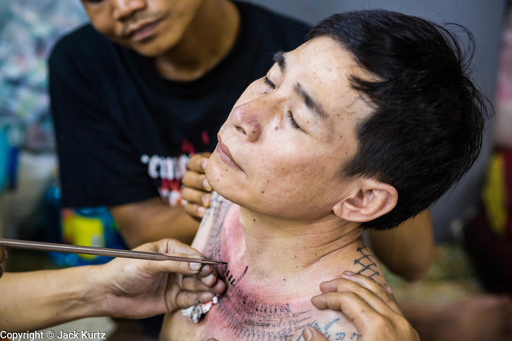 """22 MARCH 2013 - NAKHON CHAI SI, NAKHON PATHOM, THAILAND: A man gets a sacred Sak Yant tattoo at Wat Bang Phra during the tattoo festival. Wat Bang Phra is the best known """"Sak Yant"""" tattoo temple in Thailand. It's located in Nakhon Pathom province, about 40 miles from Bangkok. The tattoos are given with hollow stainless steel needles and are thought to possess magical powers of protection. The tattoos, which are given by Buddhist monks, are popular with soldiers, policeman and gangsters, people who generally live in harm's way. The tattoo must be activated to remain powerful and the annual Wai Khru Ceremony (tattoo festival) at the temple draws thousands of devotees who come to the temple to activate or renew the tattoos. People go into trance like states and then assume the personality of their tattoo, so people with tiger tattoos assume the personality of a tiger, people with monkey tattoos take on the personality of a monkey and so on. In recent years the tattoo festival has become popular with tourists who make the trip to Nakorn Pathom province to see a side of """"exotic"""" Thailand. The 2013 tattoo festival was on March 23.    PHOTO BY JACK KURTZ"""