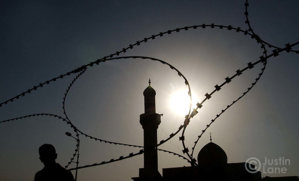 08/13/03  Baghdad, Iraq  Attn: Foriegn-- Barbed wire, a mosque and a passing pedestrian are silhoutted against the setting sun in Baghdad this afternoon.