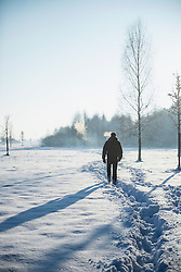 Rear view of a man walking on snow covered landscape during winter, Bavaria, Germany