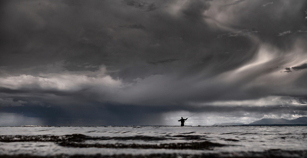 A fly fisherman casts his line as a rain storm crosses the Strait of Georgia near Sechelt, BC. (2018)