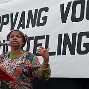 Vrouwen Tegen Uitzetting (VTU) voert op 14 april 2012 een 'lig-actie' op de Dam.Tégen het op straat zetten van vluchtelingen, vóór fatsoenlijke opvang.VTU is een netwerk van Nederlandse en vluchtelingenvrouwen met en zonder verblijfsvergunning. VTU zet zich in voor een goed asielbeleid en aandacht voor de positie van vrouwelijke vluchtelingen.Het protest richt zich in de eerste plaats tegen het op straat zetten van vluchtelingen en pleit voor fatsoenlijke opvang. Maar er komt meer aan de orde. Diverse sprekers belichten of bezingen het wetsontwerp over 'gewortelde kinderen', het Kinderpardon, de schandalig hoge legeskosten en de slordige, haastige, asielprocedure.Om 15.00 u worden één voor één de namen van vluchtelingen  opgelezen die op straat zijn gezet, terwijl de aanwezigen op de Dam gaan liggen om te laten zien hoeveel asielzoekers op straat moeten leven.Sprekers zijn o.a. Vincent Bijloo cabaretier; Marieke Doorninck (Groen Links gem Amsterdam); Khadija Arib (2e K PvdA); Tofik Dibi (2e K GroenLinks)Stephanie Mbanzendore - Burundese en Myra. Op de foto: Rinia Cromwell die op persoonlijke titel een toespraak hield. Foto JOVIP/JOHN VAN IPEREN