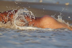 detail of a naked man's body with waves crashing over him