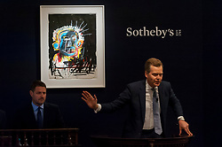 © Licensed to London News Pictures. 26/06/2018. LONDON, UK. Sotheby's Oliver Barker fields bids for ''Untitled'' by Jean-Michel Basquiat, (Est. £1,500,000 - 2,500,000) which sold for a hammer price of £3,250,000 at Sotheby's Contemporary art evening sale in New Bond Street.  Photo credit: Stephen Chung/LNP