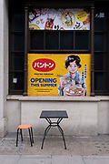 A retro poster and modern table and chair outside the Japan Centre off Leicester Square, in Panton Street, on 15th July 2021, in London, England. Japan Centre sells imported Japanese edibles and cookware, plus beauty products and manga comics.