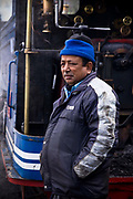 "Train driver Birkh Dattani drives the narrow gauge steam train between Darjeeling and Kurseong, the shorter of the two  journeys he has been traveling for the past  40 years. The Darjeeling Himalayan Railway, nicknamed the ""Toy Train"", is a narrow-gauge railway from Siliguri to Darjeeling in West Bengal, run by the Indian Railways. It was built between 1879 and 1881 and is about 86 km long. The elevation level is from about 100 m at Siliguri to about 2200 m at Darjeeling. It is still powered by a steam engine and travels daily between the two towns, as well as a shorter route to Kurseong.  It is now classed as a World Heritage Site by UNESCO. India."