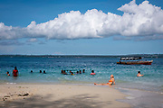 A tourist sunbathing on the white sand beach of Changuu island, also known as prison island, Zanzibar, Tanzania. Tourists visit the island on a daily basis to enjoy the beaches and see the tortoises from Stone Town, Zanzibar.