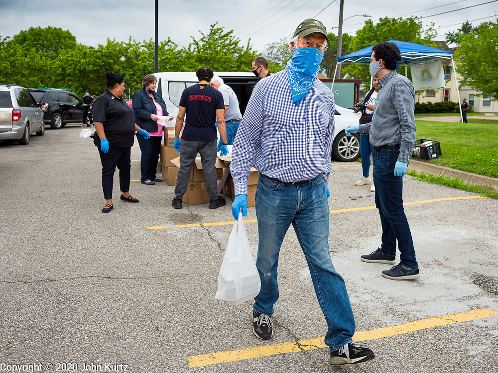 21 MAY 2020 - DES MOINES, IOWA: FRANK COWNIE, the mayor of Des Moines, carries a bag of meals to people in a drive through emergency food distribution in Evelyn K. Davis Park in central Des Moines. All of the 485 meals were distributed in about an hour. The economic fallout of the pandemic is being felt throughout Iowa. On May 21, 2020, Iowa reported that 187,375 people had filed for unemployment since the beginning of the COVID-19 pandemic and resulting economic shutdown. Emergency food pantry has also increased in that time, as many Iowans in low wage jobs used emergency food banks and pantries for the first time. The Food Bank of Iowa said Thursday that demand in April 2020 was 31% higher than demand in April 2019, mostly because of unemployment caused by the Coronavirus (SARS-CoV-2) pandemic. The emergency food distribution Thursday was organized by the city of Des Moines, Food Bank of Iowa, Central Iowa Shelter and Services, Urban Dreams and Orchestrate Hospitality.      PHOTO BY JACK KURTZ