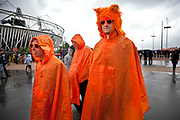 London 2012 Olympic Park in Stratford, East London. Dutch fans in orange rain coats brave the rain as weather hits the site. One fan looks oddly like ET, the Extra Terrestrial.