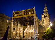 The float with the Virgin Mary, surrounded by lit candles, leaves Seville Cathedral at the blue hour. Andalusia, Spain