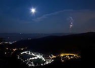 West Point, New York - The moon and a lightning bolt in the sky above the U.S. Military Academy at West Point on July 4, 2012. The United State Military Academy Prep School is at lower left.