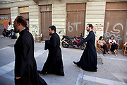 Street scene in Monastiraki. Greek Orthodox Church priests pass by wearing their black robes. Athens is the capital and largest city of Greece. It dominates the Attica periphery and is one of the world's oldest cities, as its recorded history spans around 3,400 years. Classical Athens was a powerful city-state. A centre for the arts, learning and philosophy.