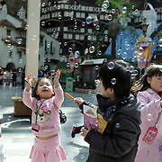 Young Korean children enjoy bubbles sprayed at Lotte World. Lotte World is the world's largest indoor theme park which includes shopping malls, a luxury hotel, and an Ice rink. Opened on July 12, 1989, Lotte World receives over 8 million visitors each year. Seoul, South Korea. 21st March 2012. Photo Tim Clayton