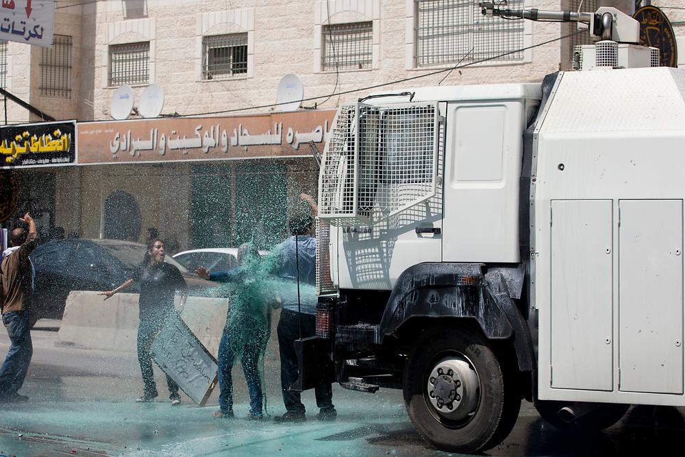 Palestinian protesters block a police anti-riot car during clashes with Israeli troops at the Qalandiya checkpoint, between Jerusalem and the West Bank city of Ramallah on June 5, 2011.