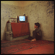 A boy watches TV inside an abandoned building in the outskirts of Kabul.