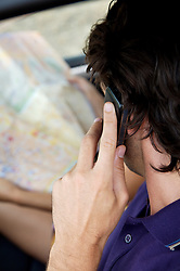 Close up of young man looking at map whilst on the telephone