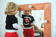 Young toddler of two looks at herself in the mirror