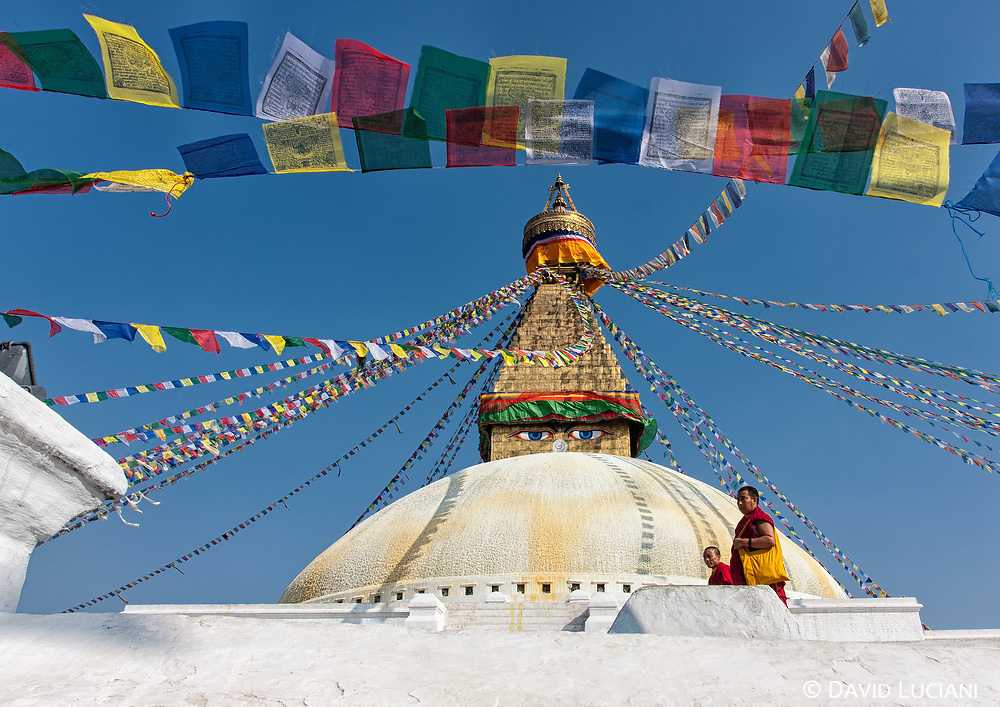 Two Buddhist monks walking around Boudhanath stupa, one of the largest stupa in the world. The Buddhist site of Boudhanath is located in Kathmandu and easily reachable for tourists.