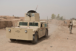 © Licensed to London News Pictures. 11/09/2015. Kirkuk, Iraq. A Kurdish peshmerga fighter watches an armoured humvee move through the recently captured village of Zankhar, Iraq. The village was captured by the peshmerga during an offensive to expand a safety zone around Kirkuk, Iraq.<br /> <br /> The offensive, which went unchallenged after ISIS left the area ahead of the attack, saw the peshmerga capture 15 villages along the Kirkuk front line. The objective of the offensive was to expand the safety zone around Kirkuk, stopping militants from firing missiles and rockets in to the city of Kirkuk. 3 peshmerga were killed and 24 wounded due to improvised explosive devices left behind by the militants. Photo credit: Matt Cetti-Roberts/LNP