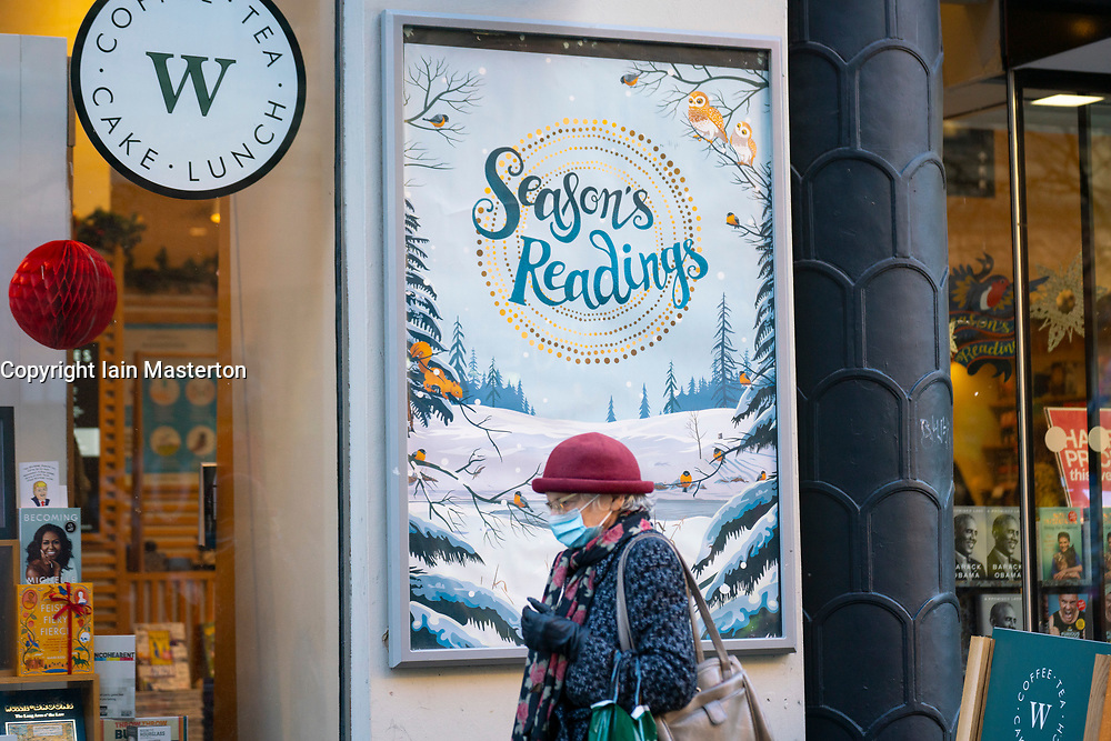 Glasgow, Scotland, UK. 19 November 2020. On the day before the highest level 4 lockdown is imposed on west and central Scotland, shops in Glasgow city centre and streets are busy with members of the public. Pictured; Woman walks past Waterstones bookshop with Season's Readings poster in window.   Iain Masterton/Alamy Live News