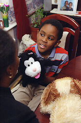 Social worker and young boy playing with puppets,