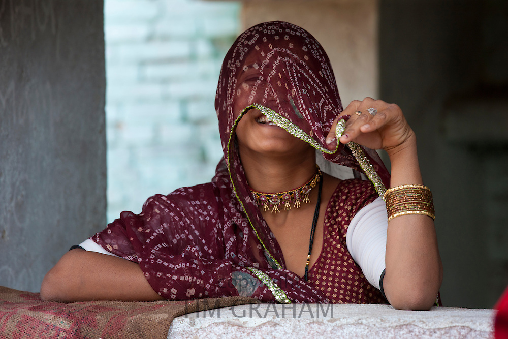 Pretty young Indian woman covering her face at home in Narlai village in Rajasthan, Northern India