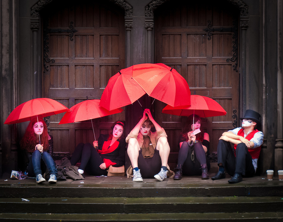 performers wait in the rain before their act in the Edinburgh festival in Scotland.