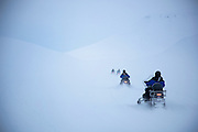 Snow mobiles follow tracks in the icy landscape of Spitsbergen, the largest island in the arctic Svalbard archipelago in Norway