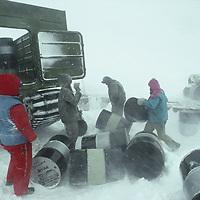 ANTARCTICA. Queen Maud Land. Russian workers load empty fuel drums in storm at Novolazarevskaya science base.