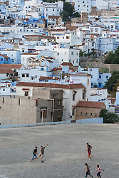 People playing soccer below view of Chefchaouen and the Rif Mountains, Morocco