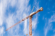 Orange construction crane with a blue sky and light white clouds background