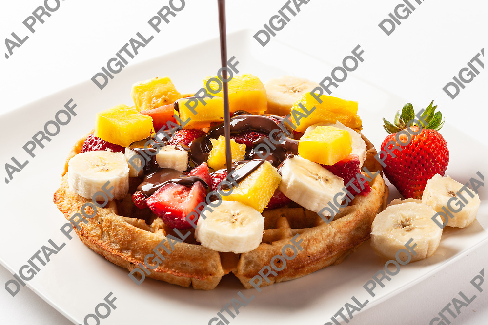 Waffle topped with strawberry, banana and orange fruits and dark chocolate being poured isolated in studio with a white background